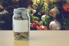Money in the glass bottle with decorated Christmas tree. Background blur Stock Photography