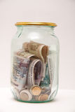 Money in the glass jar. On light background Royalty Free Stock Photos
