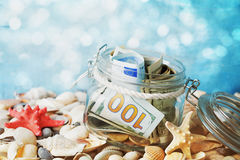 Money in glass jar on bokeh background. Savings for summer holidays, vacation, travel and trip. royalty free stock photos