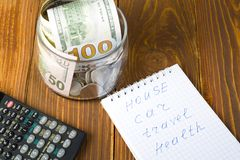 Money in glass jar,calculator and notepad with words HOUSE,TRAVEL, CAR and HEALTH . Family budget concept. Words HOUSE,TRAVEL CAR and HEALTH on paper of notepad Royalty Free Stock Photography
