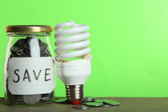 Money in a glass jar and a light bulb Stock Photos