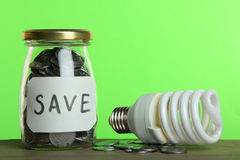 Money in a glass jar and a light bulb Royalty Free Stock Image