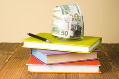 Money in glass jar on stack of books on wooden table.Saving,financial and education concept. Money in glass jar.pen on stack of colorful books on wooden table Royalty Free Stock Image
