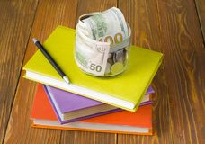 Money in glass jar on stack of books on wooden table.Saving,financial and education concept. Money in glass jar.pen on stack of colorful books on wooden table Stock Images