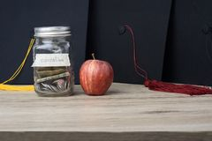Money in a glass jar put on the table for university study. stock image