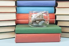 Money in glass jar and stack of books on wooden table.Saving, financial and education concept. Money in glass jar and stack of books on wooden table.Concept of Stock Photo