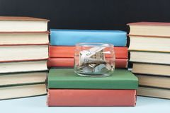 Money in glass jar and stack of books on wooden table.Saving, financial and education concept. Money in glass jar and stack of books on wooden table.Concept of Royalty Free Stock Images