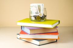 Money in glass jar and stack of books on wooden table.Saving, financiai and education concept. Money in glass jar and stack of books on wooden table against Stock Photography