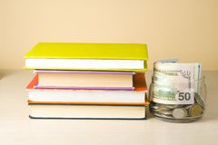 Money in glass jar and stack of books on wooden table.Saving, financiai and education concept. Money in glass jar and stack of books on wooden table against Royalty Free Stock Image