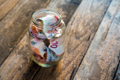 Money. In glass jar on wooden table Stock Photo