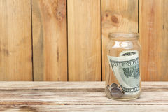 Money in glass jar on wooden table Stock Image
