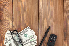 Money, glasses and car key on wooden table Stock Images