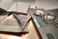 Money, glasses pen and laptop. Royalty Free Stock Image
