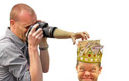 Money grabbing camera hand. Concept photo of a hand coming from inside a zoom lens ready to grab money from men wearing golden crown Royalty Free Stock Image