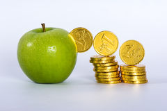 Money into green apple Royalty Free Stock Photos