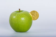 Money into green apple Stock Photography
