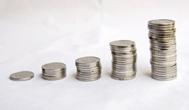 Money grow. Several stacks of  coins grow from one to many on white background Royalty Free Stock Photo
