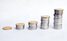 Money grow. Several stacks of  coins grow from one to many on white background Royalty Free Stock Photos