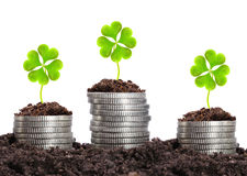 Money growth. Silver coins in soil with cloverleaf Royalty Free Stock Image