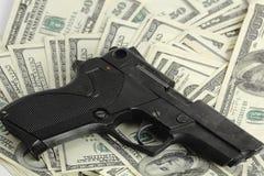 Money and gun. Gun on the dollars background Stock Photos