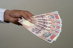 Money in hand. Close up of a  hand with indian currency holding tousand rupee notes Stock Photos