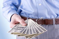 Money in the hand of the businessman. Here's you cash stock photo