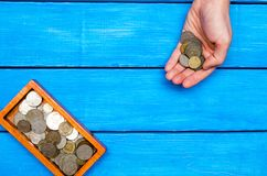Money in hand, casket with coins on a blue wooden background, sp Royalty Free Stock Image