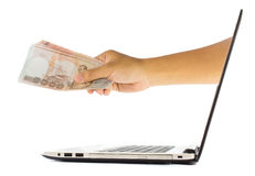 Money in hand grom laptop Stock Photo