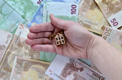 Money and a hand with a house Royalty Free Stock Images