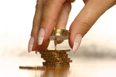 Money and hand. A hand picking up (or stacking up) some coins Stock Photo