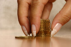 Money and hand. A hand picking up (or stacking up) some coins royalty free stock photo