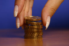 Money and hand. A hand picking up (or stacking up) some coins Stock Image