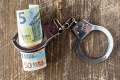 Money and handcuffs. Royalty Free Stock Photos