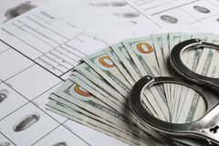 Money, handcuffs and fingerprint record sheets, closeup. Criminal investigation royalty free stock photo