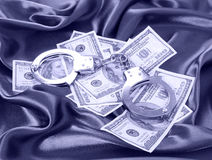 Money and handcuffs on silk fabric Stock Photography