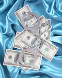 Money and handcuffs on turquoise silk fabric Stock Photos