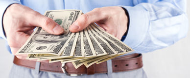 Money in the hands of the businessman. Here's you cash stock photos