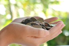 Money in the hands of the girl. Many coins in the hands of young women.To use to pay.on blurred background stock image