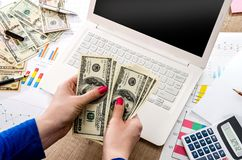 Money in the hands of a laptop. And graphics Royalty Free Stock Photos