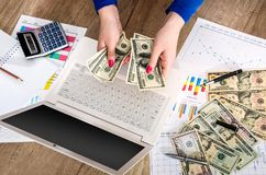Money in the hands of a laptop. And graphics Royalty Free Stock Images