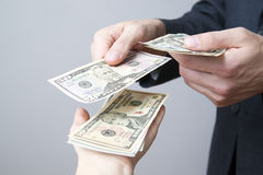 Money in the hands of the people. Convert dollars on gray background Royalty Free Stock Image