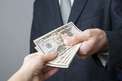 Money in the hands of the people. Convert dollars on gray background Royalty Free Stock Photography