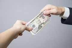 Money in the hands of the people. Convert dollars on gray background Royalty Free Stock Photo