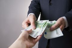 Money in the hands of the people. To count euro on gray background Royalty Free Stock Photo