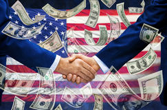 Political Money Handshake American Business Trump. A pair of businessmen shaking hands with an American flag and money falling down around them Royalty Free Stock Images