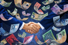 Money Handshake Australia Business. A pair of businessmen shaking hands with Australian money falling down around them Royalty Free Stock Image