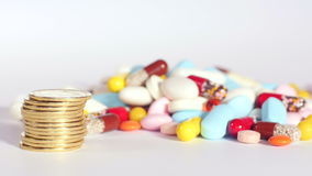 Money for health. Pile of golden coins rises up on foreground, various pills on background, concept of health, buying medication, spending money on health. Close stock video