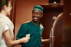 Money for help. Young guest of hotel giving porter money for his help stock photography