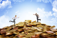 Money hill. Businesspeople running on money coins hill royalty free stock photos
