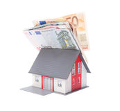 Money and house. Housing finance, building savings and realty financing (investments) concept. Money on model of the family house roof Stock Photo